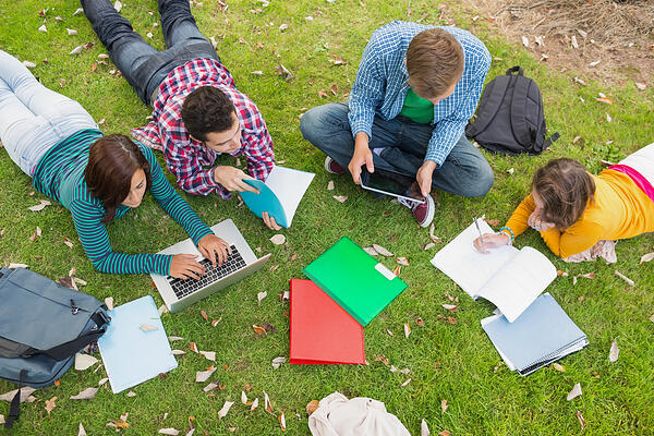 High angle view of young college students using laptop while doing homework in the park